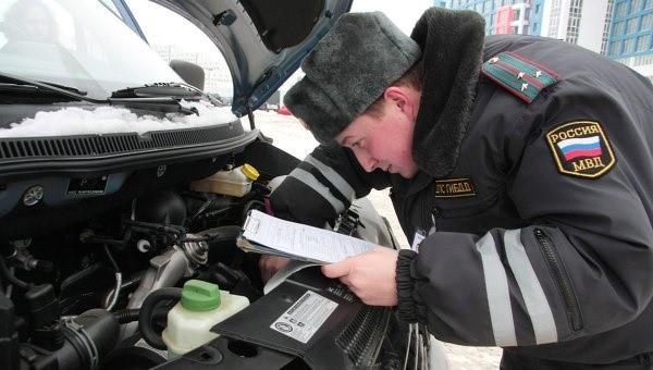 Работник ГИБДД сверяет идентификационный номер на двигателе с тем, который указан в бумагах